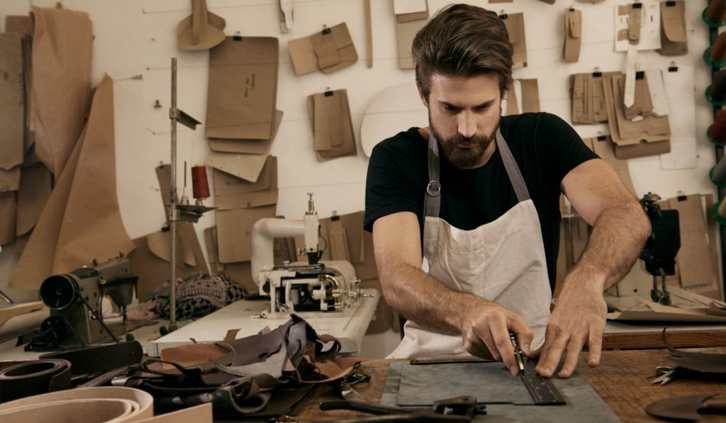 man cutting out leather
