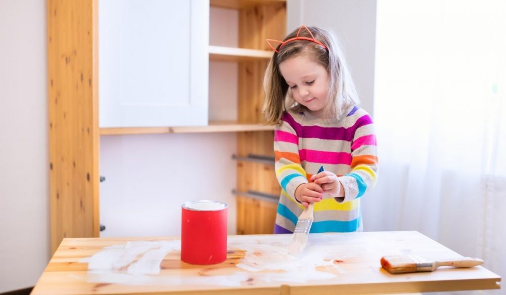 a preschool girl holding a brush painting the wooden table with white paint