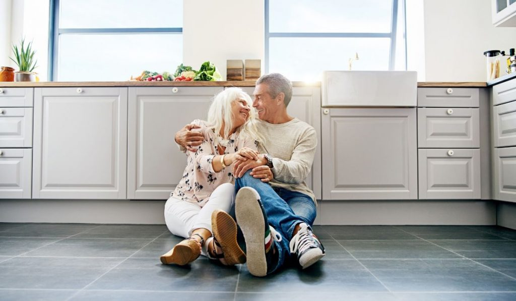 cute senior couple smiling at each other while sitting on the kitchen floor