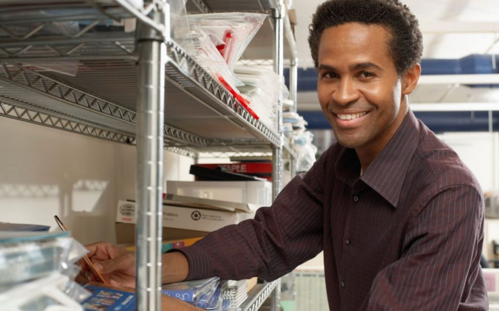 man using storage shelves for office supplies
