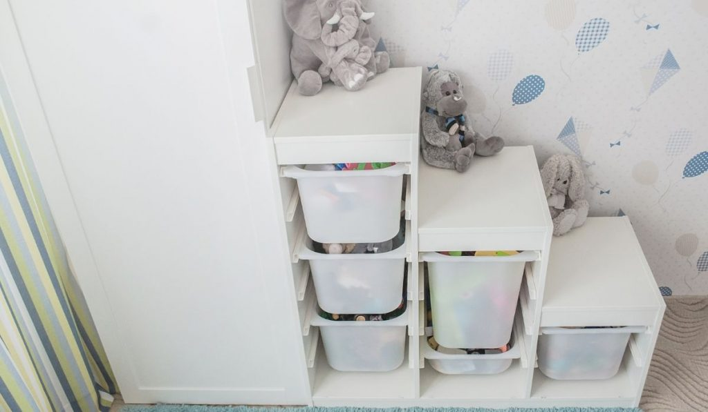 white vertical cabinet beside the toy storage drawers