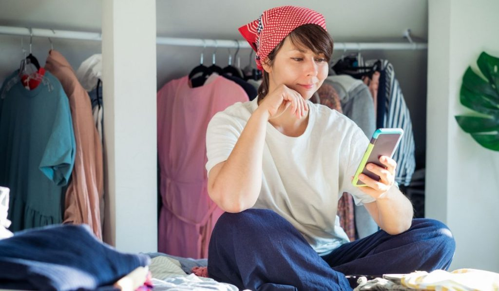 girl sitting down browsing her phone and sorting her clothes